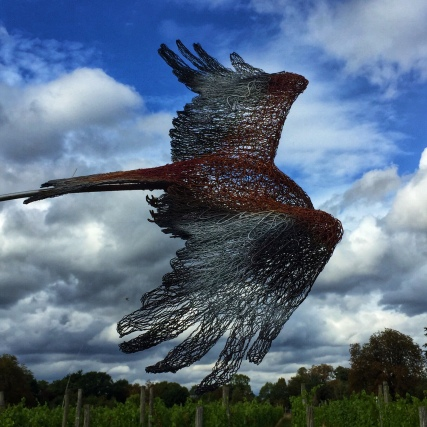 Wire bird sculpture highlighted against blue sky at Bothy Vineyard, Oxfordshire, sculpture in the vineyard