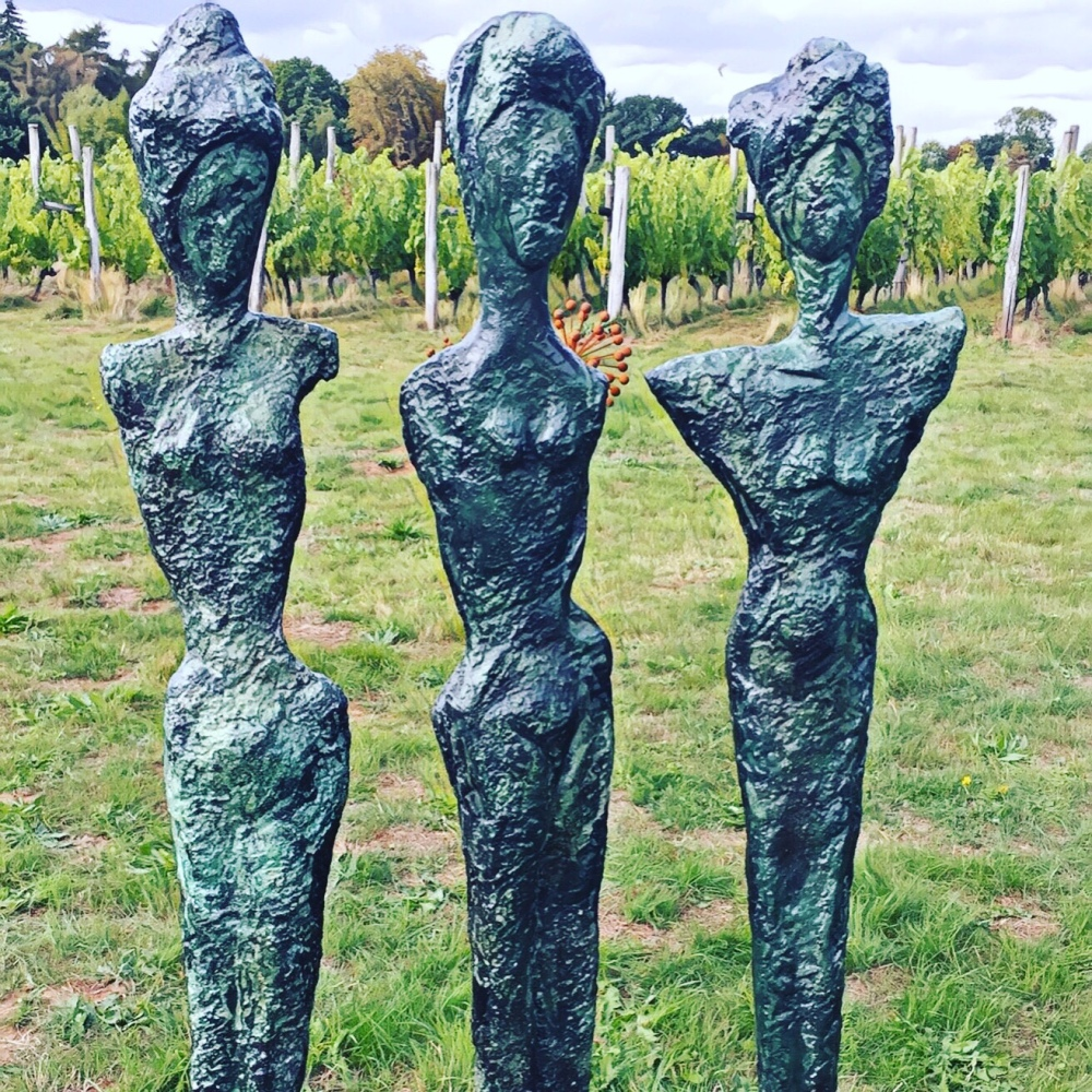 Female form sculptures with vines background at Bothy Vineyard, Oxfordshire, sculpture in the vineyard
